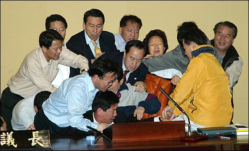 김성조, 이병석 한나라당 의원들이 의장석에 앉아 있던 정세균 우리당 의원을 끌어내려 하자, 우리당 의원들이 달려들어 이를 제지하고 있다. 김성조, 이병석 한나라당 의원들이 의장석에 앉아 있던 정세균 우리당 의원을 끌어내려 하자, 우리당 의원들이 달려들어 이를 제지하고 있다.